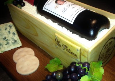 Wine Bottle Cake £240. Wine bottle, box and 'cheese' all in chocolate sponge with white chocolate 'sawdust', fondant biscuits and grapes.