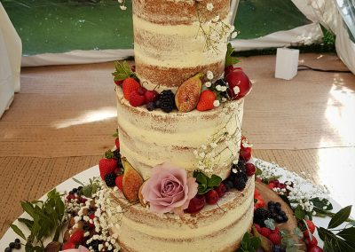 Tall semi-naked wedding cake in vanilla sponge with dark berries, herbs and flowers £595