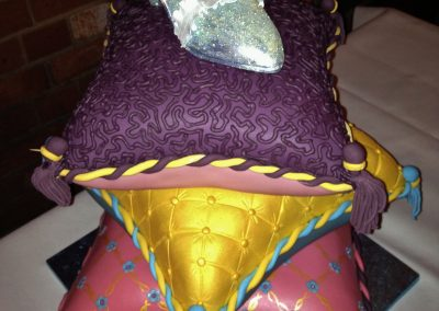 Cinderella's Slipper £585. Sparkling sugar slipper on a stack of cushions in chocolate, lemon and vanilla cake covered with fondant.