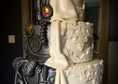 Dr Who Wedding Cake. Three large tiers of sponge in chocolate and vanilla. One half decorated in traditional wedding stylr, the other in 'Dr Who' style steam punk machinery with flashing red lights built in. £785