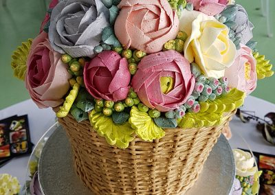 Multi Colour Flower Basket Cake. soft sponge cake filled and iced with buttercream to  represent basket weave and flowers. £245