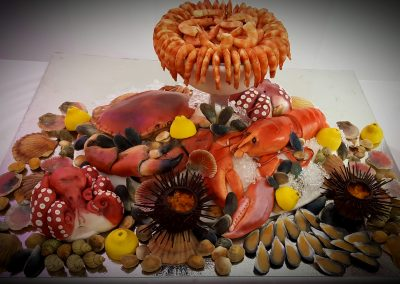 Seafood Extraveganza £1,850. Various sponge cakes in different flavours to represent shellfish, octopi and goblet bowl, with white chocolate prawns, hand-painted white