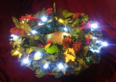 Christmas Wreath £385. Extravegant Christmas fruit cake in a ring, decorated with miriad sugarpaste leaves and berries, royal icing pine needles and hand-modelled chocolate  fir cones.... Lit with battery operated fairy lights.