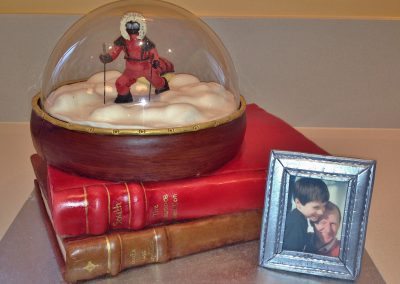 Polar Explorer Cake £485. Snow dome and books in chocolate cake covered with fondant... edible photo in fondant frame on ginger biscuit.