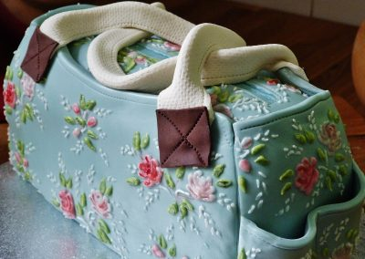 Cath Kidston style bag £185. Homage to Cath Kidston in Vanilla sponge covered with fondant icing... hand-painted and royal icing flower detail