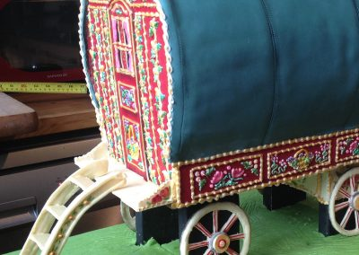 Gypsy Caravan £585. Close up of decorative detail, royal-iced in relief on to the red chocolate panels and hand painted.