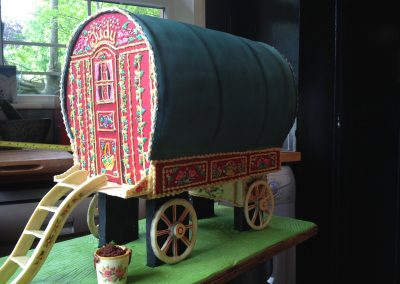 Gypsy caravan Cake £585. Huge Cake in chocolate sponge with red velvet buttercream filling. Decorated with coloured chocolate panels, detailed with hand painted royal icing designs. Canopy in fondant icing. Wheels, woodwork and steps in white chocolate.